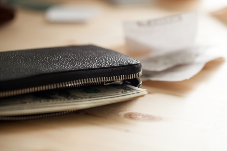 Leather wallet with cash on the wooden table with some cheques