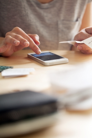 telefonok: Nő számolás pénz rá telefonon, miközben egy csekket. Van is egy bőr pénztárcát közel van a kamerához