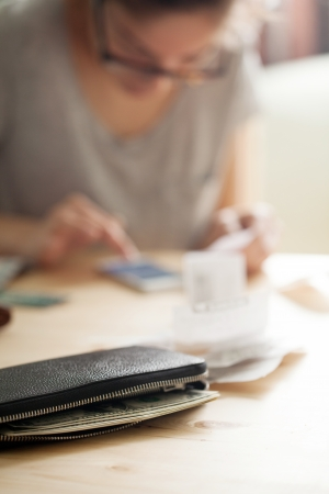 Woman is counting money on her phone while holding a cheque. There is also a leather wallet close to the camera photo