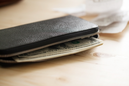 Leather wallet with cash on the wooden table with some cheques photo
