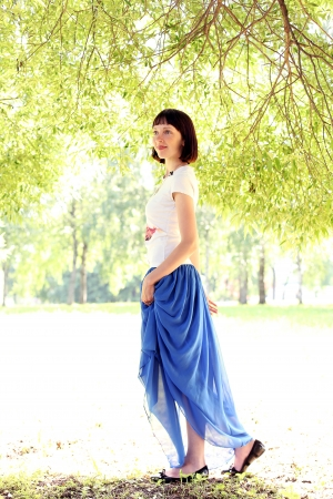 Woman in a blue skirt walking under a tree photo