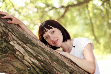 Woman is posing near a tree at a park photo