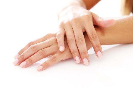 tratamientos corporales: Primer plano de las manos de mujer con manicura sobre un fondo blanco