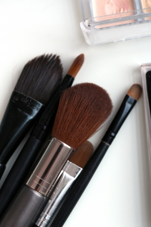 Closeup picture of a large variety of colorful cosmetic poweder and a cosmetic brush photo