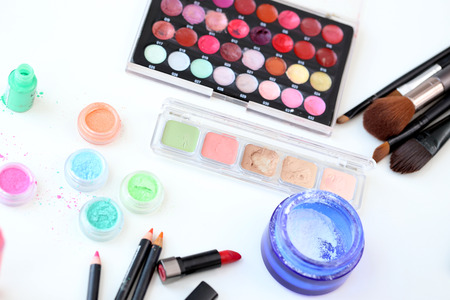 Picture of different-colored cosmetic powders with other cosmetic accessories photo