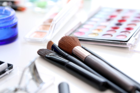 body care: Closeup picture of a large variety of colorful cosmetic poweder and a cosmetic brush Stock Photo