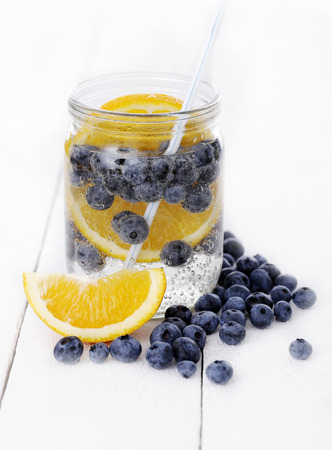A jar full of cold drink with bilberry and lemon with a straw over a white background photo