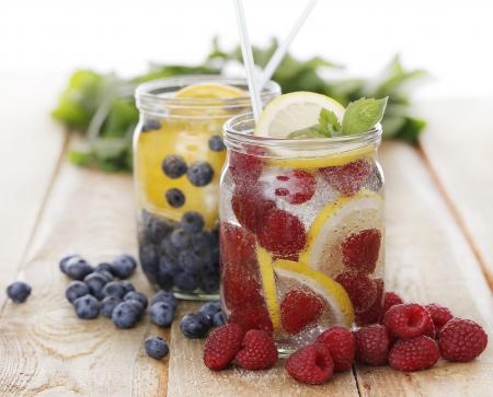 bebidas frias: Dos frascos llenos de diferentes bebidas fr�as en la mesa de madera