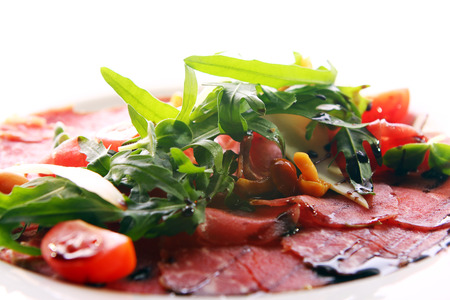 Beef carpaccio served with ruccola and mushroom photo