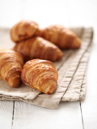 Fresh homemade french croissants on a linen tablecloth Stock Photo