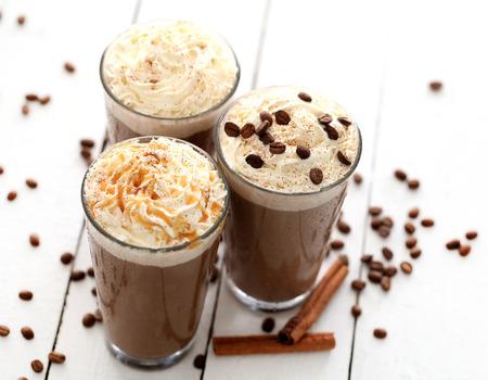 アイス コーヒーにホイップ クリームと白いテーブルの上のコーヒー豆 写真素材