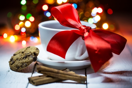 Cup of coffe with a bow on it. Few sticks of cinnamon and a cookie. The background is covered with colorful lights photo