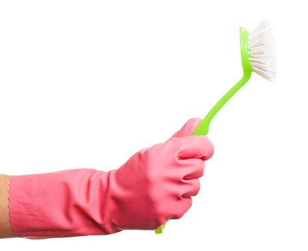 gloving up: Hand in a pink glove holding green brush isolated over white background Stock Photo