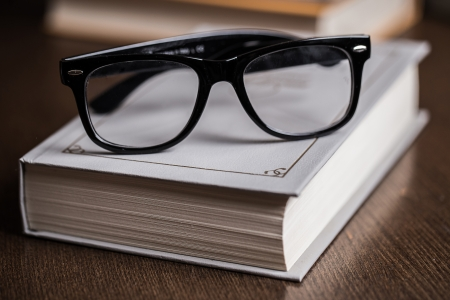 Picture of black glasses on a white book photo