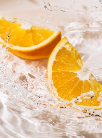 Slices of an orange splash into the water photo