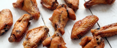 Grilled tasty chicken wings on a white wooden table  photo