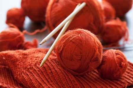 Orange knitwork with thread balls and needles in a basket
