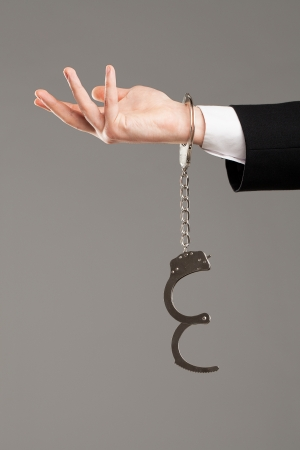 Businessman hand with opened handcuffs over grey background photo