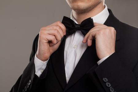 Handen raakt Man's bow-tie op een pak Stockfoto
