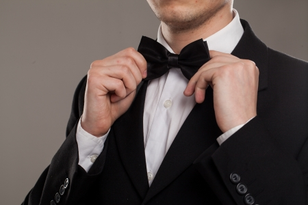 wedding suit: Mans hands touches bow-tie on a suit