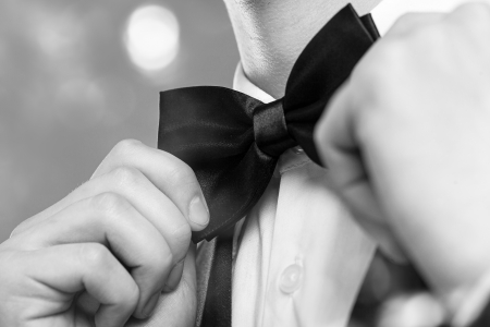 Mans hands touches bow-tie on a suit