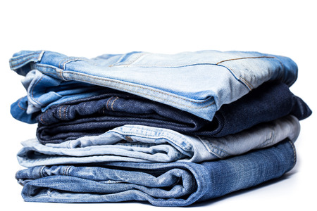 A pile of various pairs of jeans over a white background photo