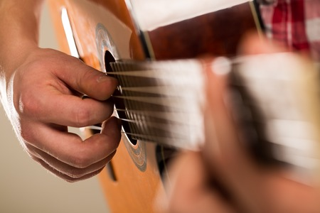 Music, close-up  Musician with a wooden guitar photo