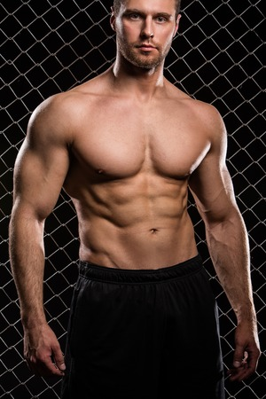 Beautiful, strong man on fence background Stock Photo