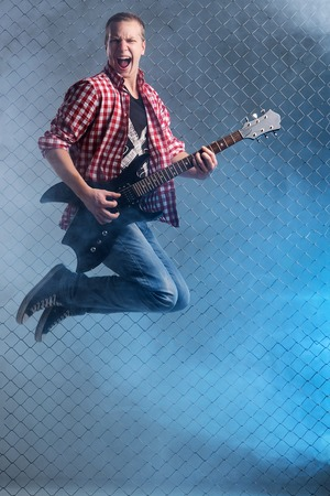Young, crazy musician with electric guitar photo