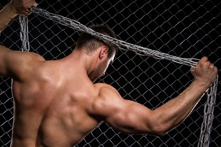 Beautiful, strong man with chain on fence  photo