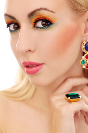 Blonde girl with jewelry has colored makeup photo