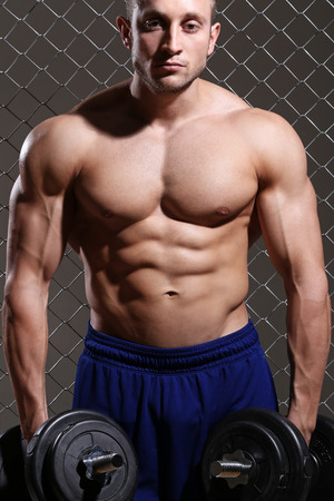 Beautiful, strong man with a dumbbell on fence background photo