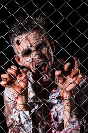 rotten teeth: Creepy zombie behind the fence