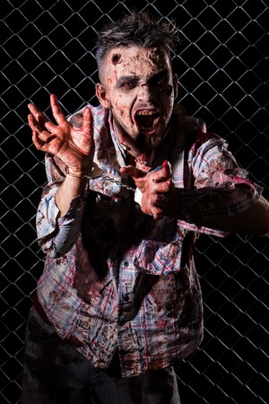 Creepy zombie in handcuffs photo