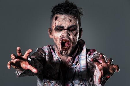 Aggressive, creepy zombie in clothes Stock Photo