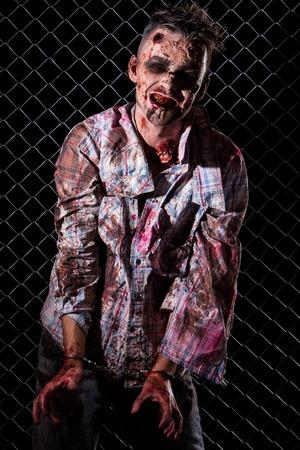 Creepy zombie in handcuffs photo