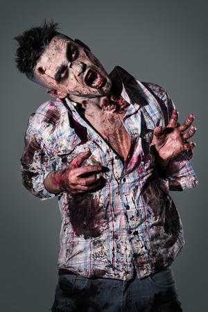 Aggressive, creepy zombie in clothes photo