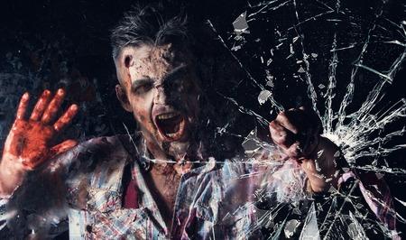 Creepy zombie breaks the window 版權商用圖片