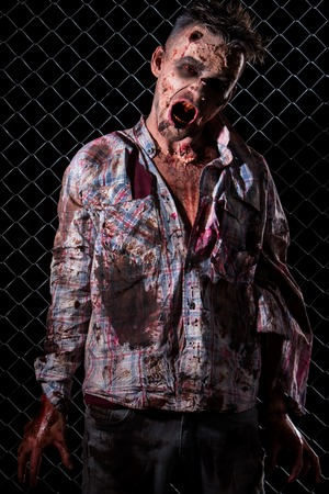 rotten teeth: Creepy zombie on the fence background