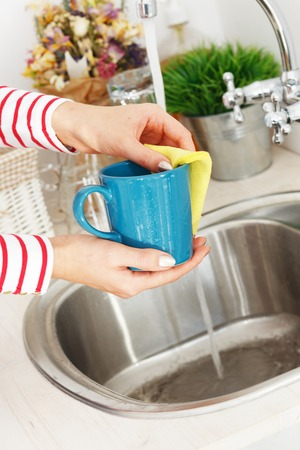 Kitchen, housework  Girl washes tea cup photo