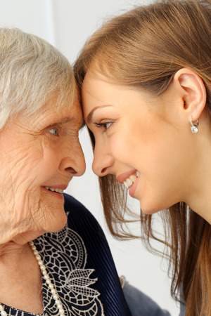 Close-up  Elderly woman and beautiful granddaughter with wide smile photo