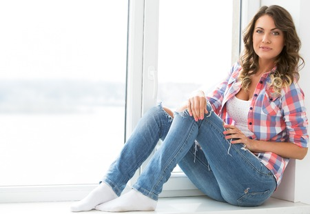 Lifestyle  Cute, attractive woman by the window Stock Photo