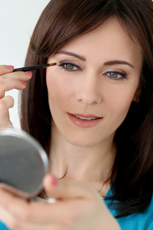 Cute, attractive woman during makeup photo