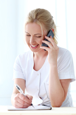 cosmetologist: Professional  Beautiful cosmetologist with mobile phone Stock Photo