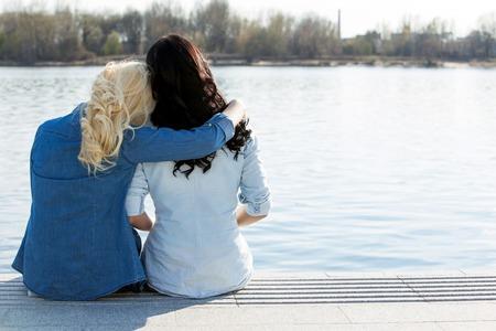 amigos abrazandose: Amistad Mejores amigos que se sientan por el río