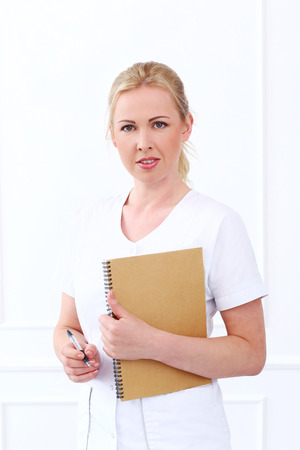 cosmetologist: Professional  Beautiful cosmetologist with notepad