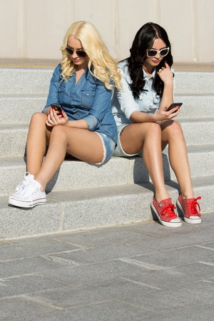 Friendship  Best friends texting on the stairs photo