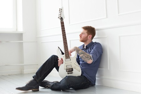 Handsome guy on the floor with electric guitar photo