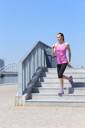 Sport, activity  Cute woman running on the street photo