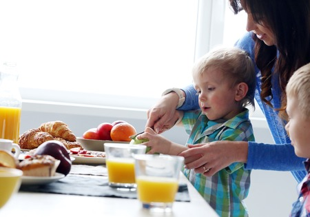 children breakfast: Mother and two brothers during family breakfast